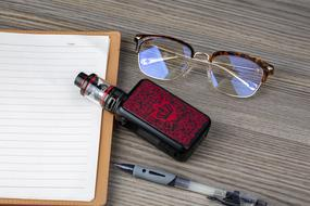 electronic cigarette, glasses, pen and open notebook