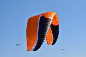 Paragliding, orange and black wing at blue sky close up