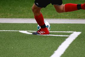 Football, male legs and ball on Pitch