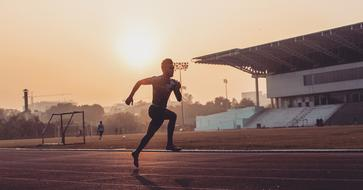 athlete runs in the stadium on a foggy morning