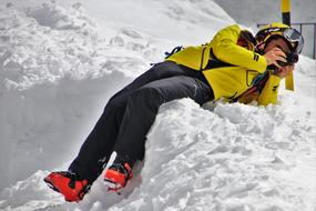 the snowboarder lies in the snow and takes pictures