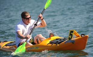 young man is kayaking with a version in his hands