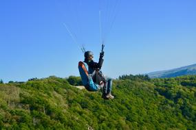 Paraglider at clean blue sky above green mountains