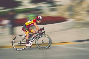 cyclist in red and yellow uniform rides at high speed in competition