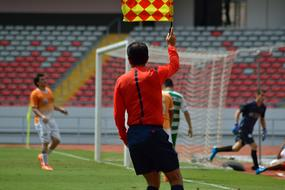 referee with yellow-red flag on the football field