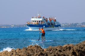 Paddleboarding, man with Paddle on board at coastline