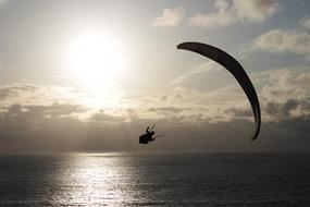 parachutist flies low over the sea