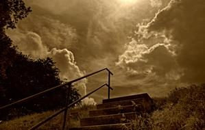 monochrome photo of stairs and railings against a cloudy sky