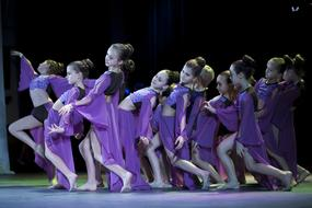 a group of girls is dancing in purple dresses