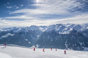 group of people skiing on Snowy Mountain side at scenic peaks