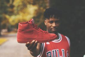 athlete holds red nike sneakers in his hand