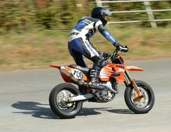 athlete standing drives a motorcycle