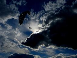 photo of a flying paratrooper against a stormy sky