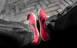 Red and black Nike shoes on the pavement