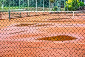 Wet tennis court with the colorful plants around