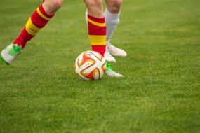 photo of footballers' feet and the ball on the field