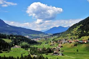 distant panorama of alpine meadows and alpine village in Switzerland