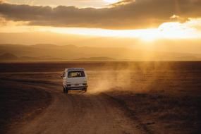 Volkswagen car driving away on dirt road at colorful sunset
