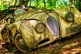 rusty oldtimer luxury Jaguar car in abandoned place
