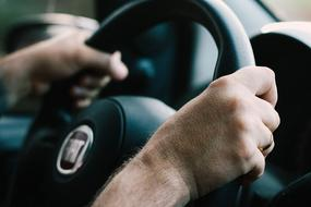 male hands on car steering wheel close up on blurred background