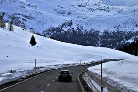 car on an asphalt road in the snowy alps