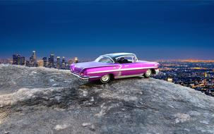 purple chevrolet impala on a rock in the background of night panorama of Las Vegas