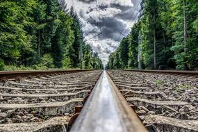 Railroad Track through forest under cloudy sky