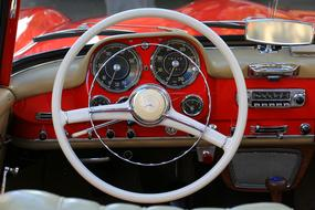 White steering wheel and dashboard of the red Mercedes car in the museum