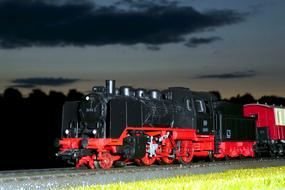 red-black steam locomotive against the background of the night sky