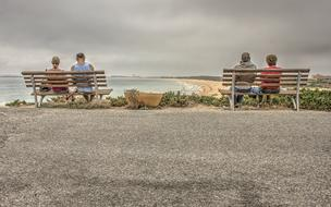 two couples are sitting on wooden benches on the sea coast