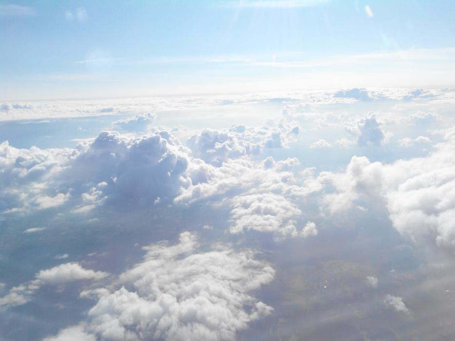 view of fluffy white clouds from an airplane window