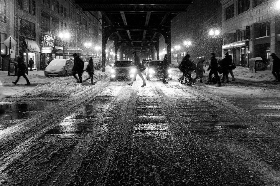 Black and photo of the people and cars on the street with with snow and lights at night in winter