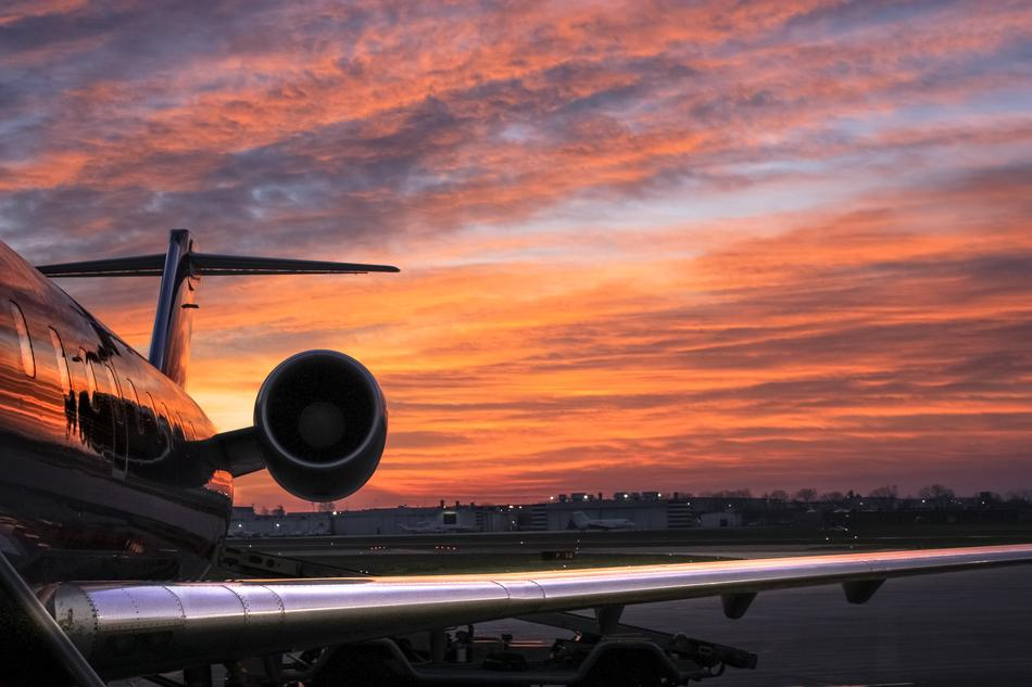 View of the side of the airplane at beautiful and colorful sunset background