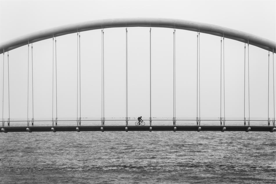 black and white photo of a biker on a suspension bridge