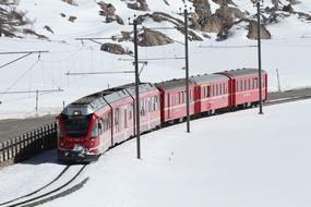 red passenger Train at snowy mountains, switzerland