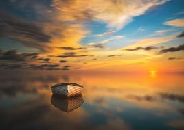 boat on calm water at colorful sunset