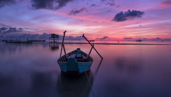 rowing boat on calm water at purple Sunrise, vietnam, phu quoc