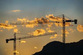 construction cranes on a background of orange clouds and the evening sky