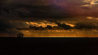 distant Sailing Vessel in Ocean at stormy sunset
