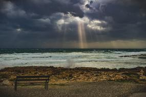 bench by the sea under a stormy sky in Ayia Napa, Cyprus