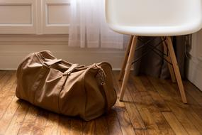 travel bag and white chair in the room