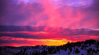 panorama of snowy mountains against a pink-purple sky in Utah