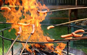 sausages are fried on a flame