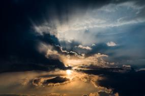 the sun's rays break through the dark clouds in the evening sky