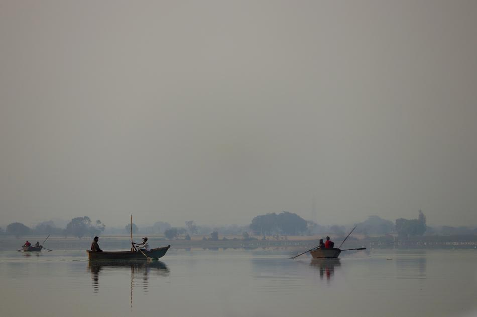 fishing boats on a lake in the fog in Asia
