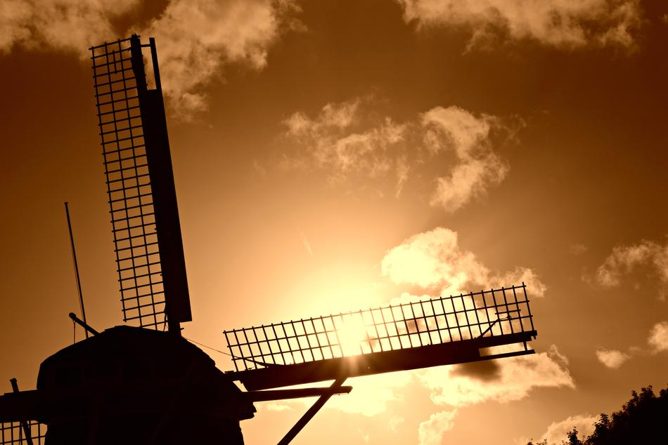 silhouette of a dutch windmill against a yellow sky