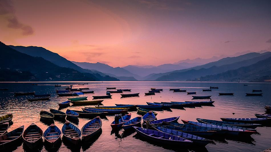 fishing boats on the lake against a pink evening sky