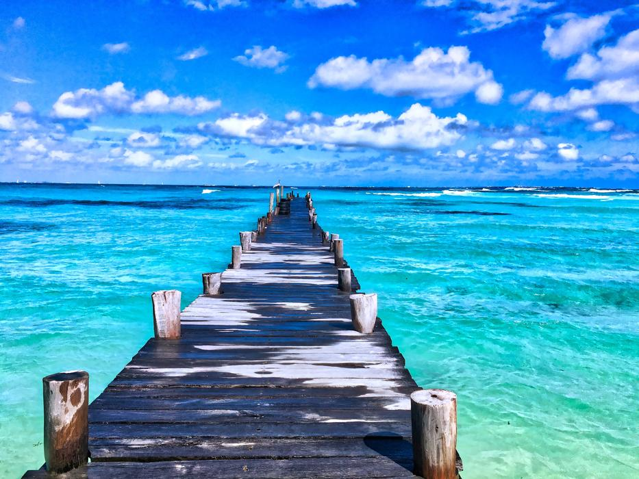 Beautiful pier of the beautiful beach among the beautiful and colorful water in Mexico