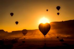 hot air balloons fly over the mountains in Turkey on the background of golden sunset