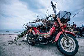 red dirty motorcycle is parked on the beach